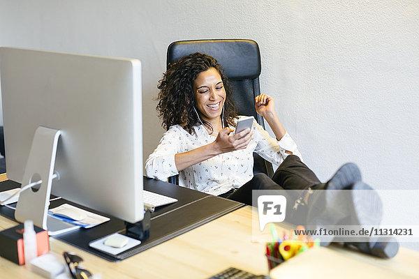 Lächelnder Geschäftsmann beim Blick auf das Handy am Schreibtisch im Büro