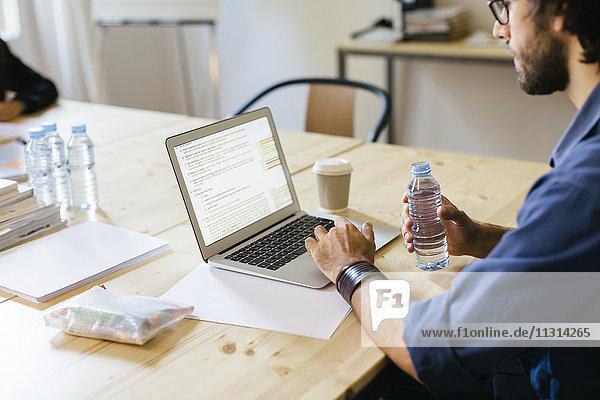 Geschäftsmann im Büro bei der Arbeit am Laptop