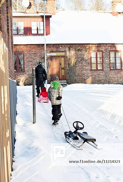 Rear view of woman with children walking and pulling sleigh