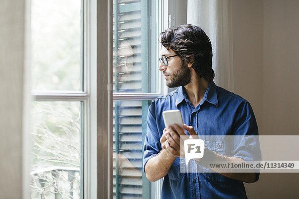 Geschäftsmann am Bürofenster stehend  mit Smartphone