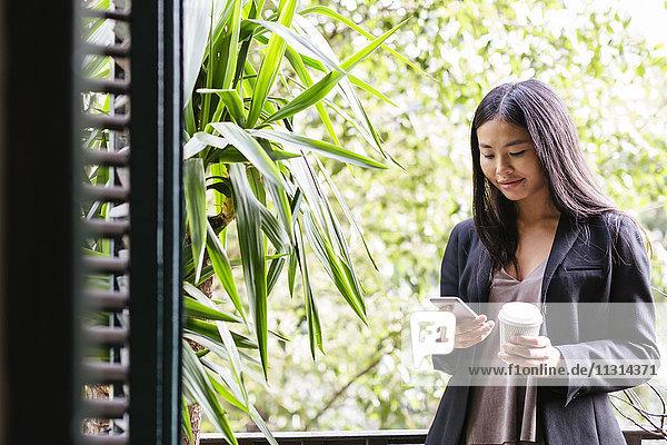 Junge Frau steht am Fenster und liest Nachrichten.