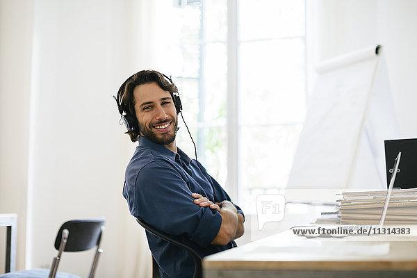 Geschäftsmann im Büro über Kopfhörer am Schreibtisch