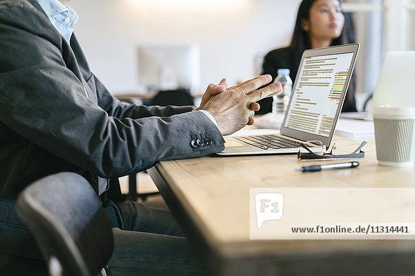 Geschäftsmann sitzt in der Sitzung  mit Laptop