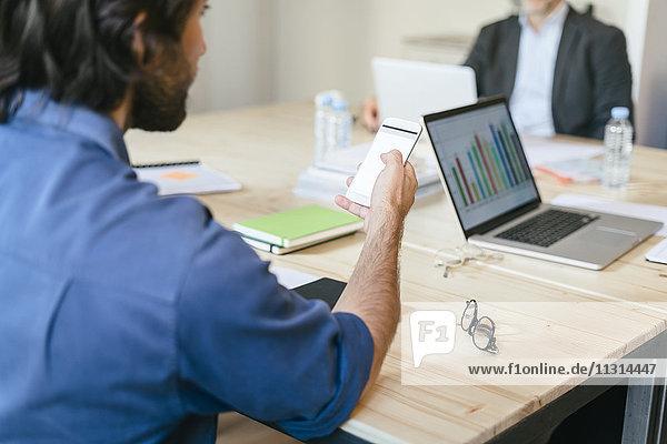Geschäftsmann mit Smartphone im Büromeeting