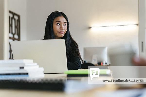 Junge Asiatin arbeitet im Büro mit Laptop