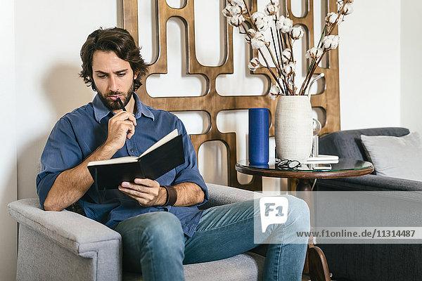 Geschäftsmann sitzt in der Bürolounge und schaut sich das Notebook an.