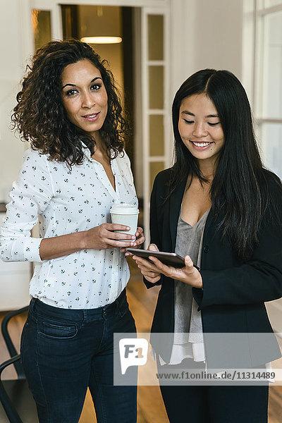 Zwei Geschäftsfrau  die Kaffee trinkt und digitale Tabletten benutzt.