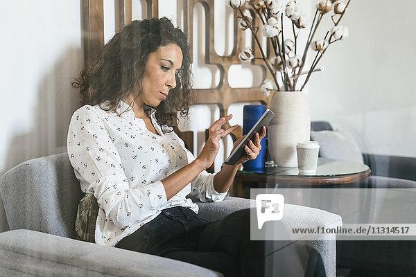Geschäftsfrau sitzend in der Lounge mit digitalem Tablett