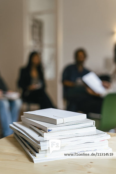 Stapel von Zeitschriften und Büchern im Regal  Geschäftsleute sprechen im Hintergrund