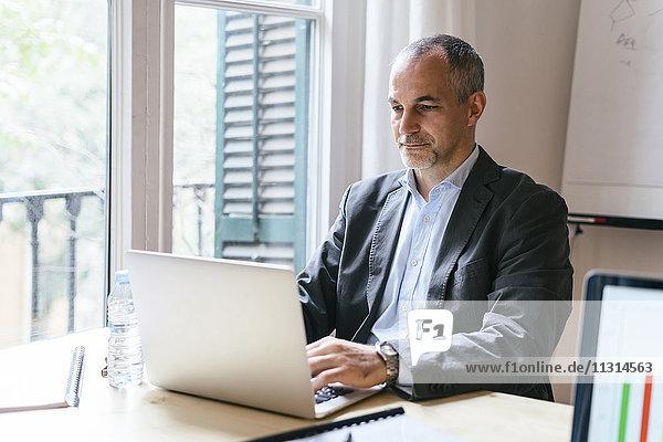 Geschäftsmann sitzt am Schreibtisch und arbeitet am Laptop