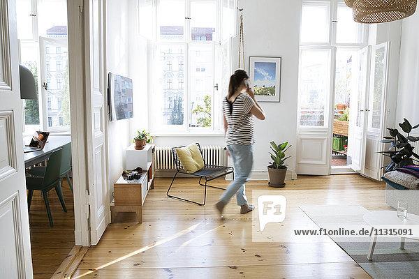 Frau zu Hause spricht am Handy