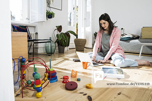 Frau zu Hause sitzend auf dem Boden mit Laptop  umgeben von Spielzeug