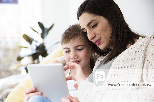 Lächelnde Mutter und Tochter zu Hause mit Tablette