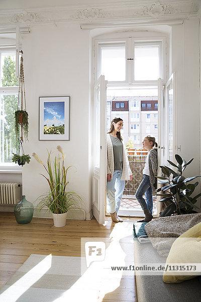 Lächelnde Mutter mit Tochter zu Hause an der Balkontür stehend Lächelnde Mutter mit Tochter zu Hause an der Balkontür stehend
