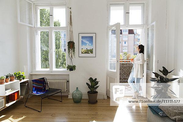 Frau zu Hause an der Balkontür stehend