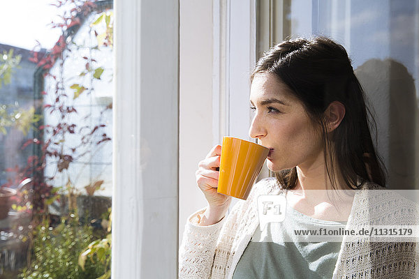 Frau trinkt Kaffee am Fenster