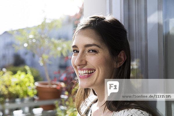 Porträt einer glücklichen Frau am Fenster
