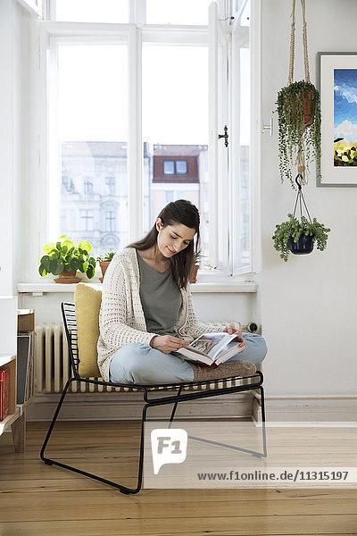 Frau zu Hause sitzend auf Stuhl Lesebuch