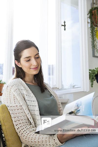Lächelnde Frau zu Hause sitzend auf dem Stuhl Lesebuch