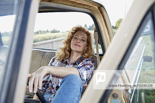 Portrait of woman sitting in pick up truck