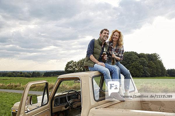 Ein Paar sitzt auf einem Pick-up und trinkt ein Bier.