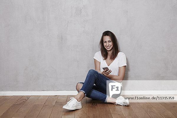 Lächelnde junge Frau auf dem Boden sitzend mit Handy