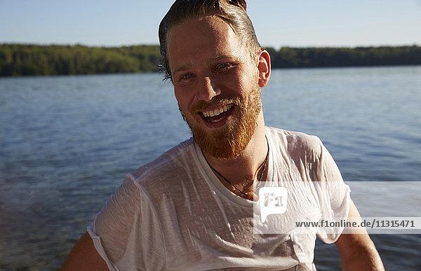 Glücklicher junger Mann mit nassem T-Shirt am See