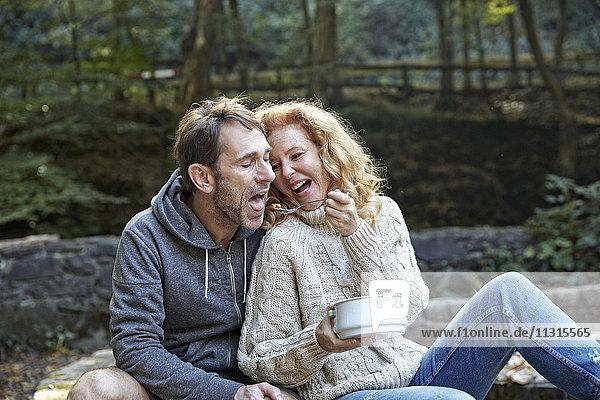 Ein glückliches Paar teilt sein Essen im Freien.