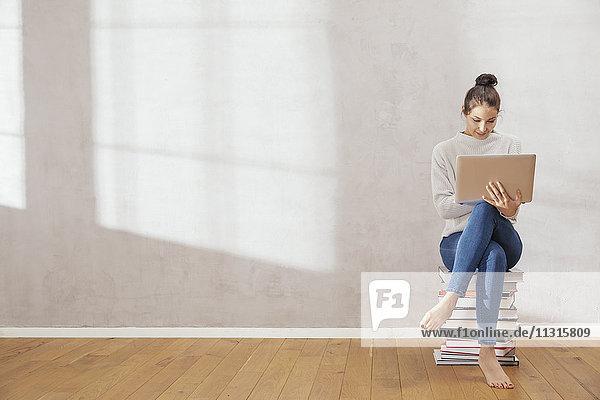 Junge Frau sitzt auf einem Bücherstapel und benutzt zu Hause einen Laptop.