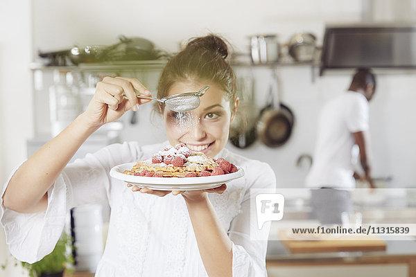 Porträt einer jungen Frau  die in der Küche Puderzucker auf Waffeln streut.
