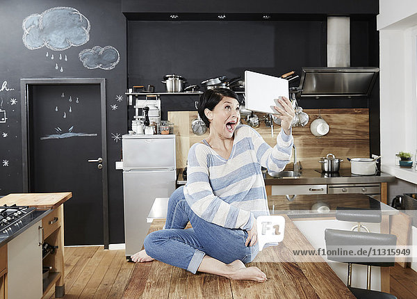 Woman sitting on table in kitchen taking a selfie with tablet