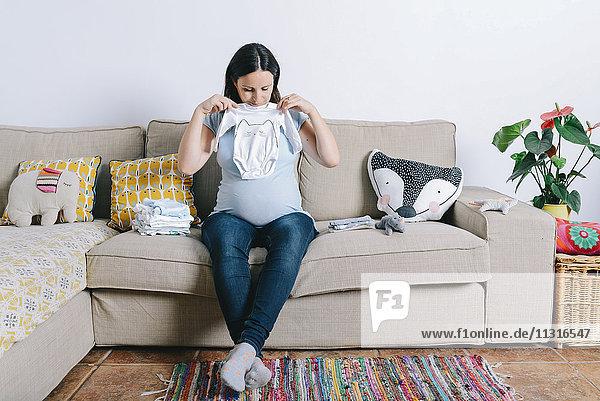 Schwangere Frau sitzt auf der Couch und schaut auf Babyschläfer. Schwangere Frau sitzt auf der Couch und schaut auf Babyschläfer.