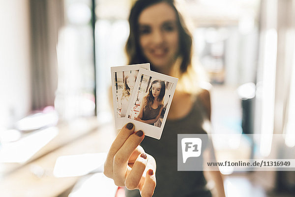 Junge Frau mit Polaroids von sich selbst