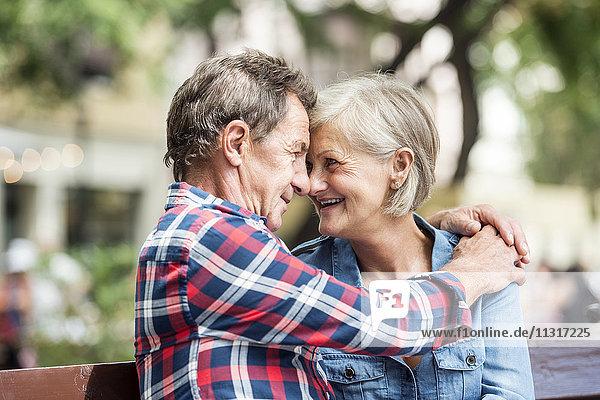 Glückliches älteres Paar sitzt Kopf an Kopf auf einer Bank