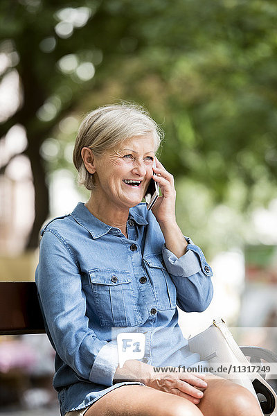 Portrait of laughing senior woman on the phone
