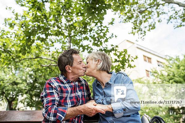 Seniorenpaar  das sich auf der Bank küsst und Händchen hält.