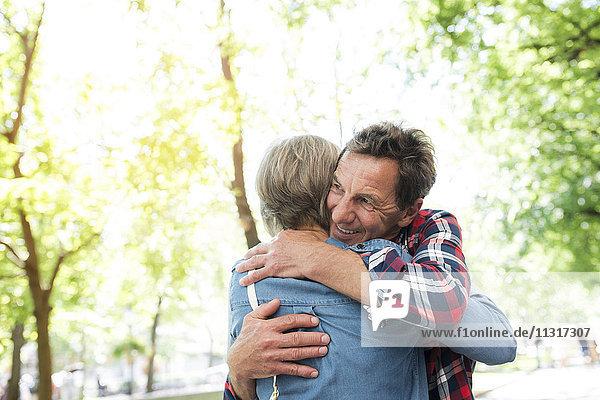 Seniorenpaar umarmt sich auf der Straße