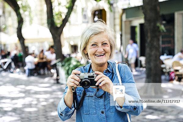 Porträt einer lächelnden Seniorin mit Kamera
