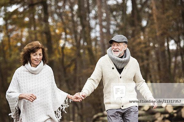 Seniorenpaar geht Hand in Hand im Wald spazieren