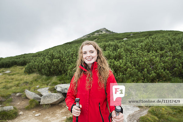 Portrait of smiling young woman on a hiking tour