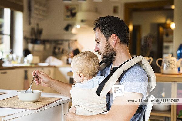 Vater füttert Baby im Tragesitz