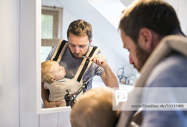 Father with baby in baby carrier brushing his teeth
