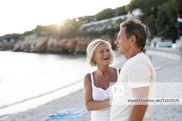 Seniorenpaar entspannt am Strand in der Abenddämmerung