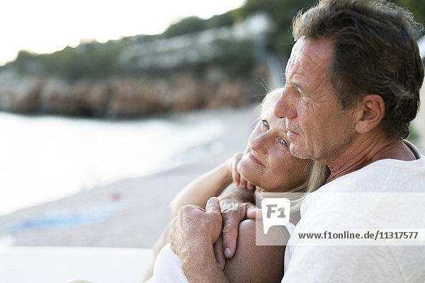 Seniorenpaar beim gemeinsamen Entspannen am Strand in der Abenddämmerung