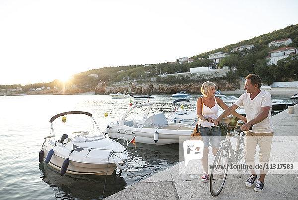 Seniorenpaar mit Fahrradwanderung am Kai in der Abenddämmerung