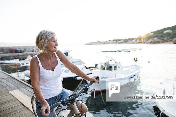 Seniorin mit Fahrrad am Steg