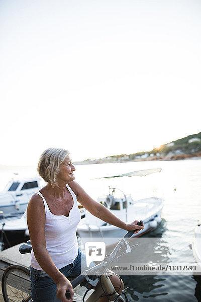 Lächelnde Seniorin mit Fahrrad vor dem Meer