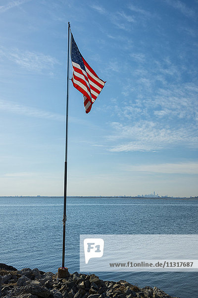 USA  New York  Queens  Jamaica Bay  American flag at Jamaica Bay looking to New York City
