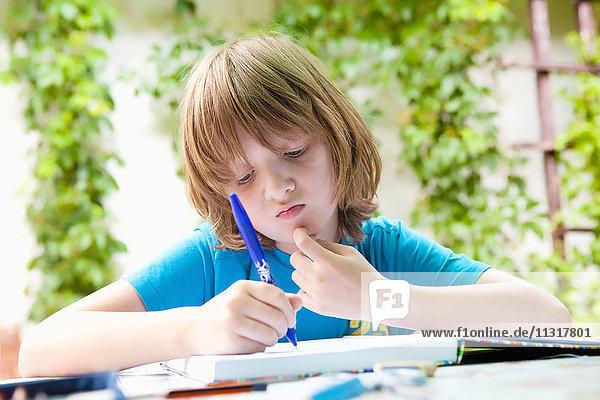 Boy with Blond Hair Doing Homework Outdoors