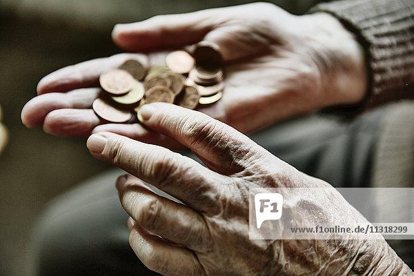 Seniorinnenhände mit Münzen